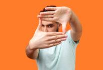 Junger Mann, der Fenster mit Händen formt