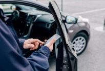 Männliche Hand mit Smartphone vor seinem Auto