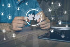 Mann hält Puzzleteile; Symbol: Outsourcing, Zusammenarbeit