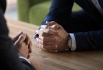 Gespräch: 2 Businesshände auf Tisch