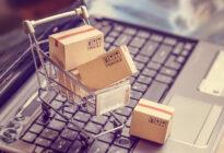 Kleiner Einkaufswagen mit Boxen steht auf Laptop