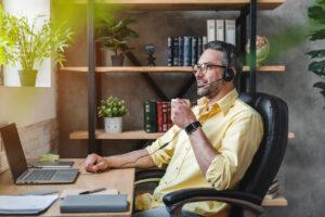Homeoffice: Mann mit Headset und Laptop am Schreibtisch Zuhause