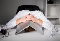Mann, der sich unter Laptop versteckt